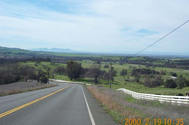The Sutter Buttes are in the distance, with the green Paradise hills in the foreground.